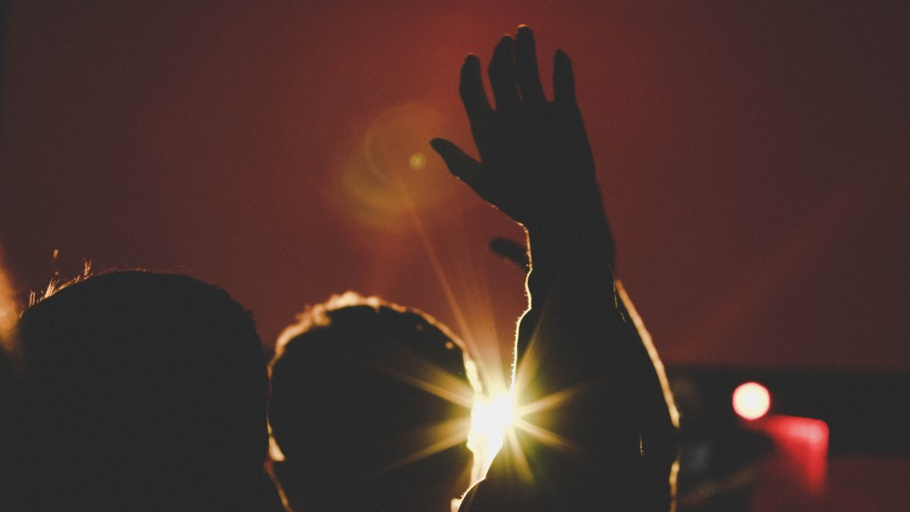 decorative - hand up in conference in front of bright light